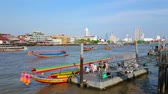 quai : BANGKOK, THAILAND - APRIL 23, 2019:  The colorful tourist speed boat waits the people at the Wat Arun pier on Chao Phraya river, on April 23 in Bangkok