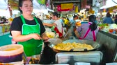 saco : CHIANG MAI, THAILAND - MAY 4, 2019: The seller of Tanin market stall cooks the tasty local puffs in deep fryer of the outdoor kitchen, on May 4 in Chiang Mai