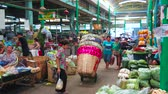 coltivazione : BANGKOK, THAILAND - APRIL 23, 2019: The narrow busy alley of central Wang Burapha Phirom agricultural market with walking visitors, sellers and porters, carrying different good, on April 23 in Bangkok