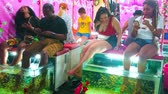 fuß : PATONG, THAILAND - MAY 1, 2019: Tourists enjoy fish pedicure in spa of Banzaan Night Bazar, excited girl is scared of tickling and unusual feelings of skin peeling by doctor fishes, on May 1 in Patong
