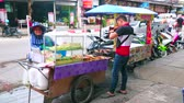 snackbar : PATONG, THAILAND - APRIL 30, 2019: The street seller at the food cart with grilled fish and chicken on skewers, on April 30 in Patong Stockvideo
