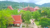 dekor : CHALONG, THAILAND - APRIL 30, 2019: The view from Wat Chalong Pagoda on the pyathat roofs and ornate details of shrines and Ubosot, hidden among the lush tropical greenery, on April 30 in Chalong