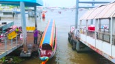 quai : BANGKOK, THAILAND - APRIL 15, 2019: The long colorful pleasure boat is moored between two piers on Chao Phraya river, on April 15 in Bangkok