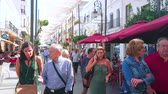 ベンチ : SANLUCAR, SPAIN - SEPTEMBER 22, 2019: The vibrant life in Calle Ancha street, full of fashion stores, cafes, restaurants and souvenir shops, attracting tourists, on September 22 in Sanlucar