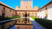 tribunal : GRANADA, SPAIN - SEPTEMBER 25, 2019: The medieval Court of Myrtles (Nasrid Palace, Alhambra) with Comares Tower and palace arcade, reflected in mirror pond, on September 25 in Granada
