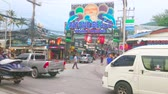 prestazioni : PATONG, THAILAND - MAY 1, 2019: Heavy traffic in tourist street with souvenir stores, market stalls, cafes, bars and travel agencies, large colorful boards and signs on background, on May 1 in Patong Filmati Stock
