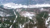 hava : OBERTRAUN, AUSTRIA - FEBRUARY 21, 2019: Dachstein-Krippenstein air tram ride with a view on winter forests, Alpine landscape and Traun river valley, on February 21 in Obertraun Stok Video