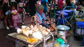menschenmenge : BANGKOK, THAILAND - MAY 12, 2019: The elderly farmer cooks boiled taro roots in small outdoor stall, located in Yaowarat of Chinatown market, on May 12 in Bangkok