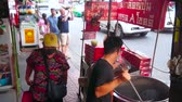 cart : BANGKOK, THAILAND - MAY 12, 2019: The small roadside food cart with a cook, making local street food - chestnuts, roasted in black sand, Yaowarat road, Chinatown, on May 12 in Bangkok
