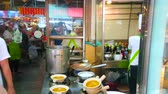 restauration rapide : BANGKOK, THAILAND - MAY 12, 2019: The kitchen of Chinese restaurant located in corridor and group of cooks prepares dishes in front of visitors, Yaowarat road, Chinatown, on May 12 in Bangkok Vidéos Libres De Droits