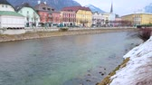 gyalogút : BAD ISCHL, AUSTRIA - FEBRUARY 20, 2019: The riverside cityscape with historical housing, tall belfry of Parish church, stone banks of Traun river and snowy Alps, on February 20 in Bad Ischl Stock mozgókép