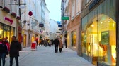 tabela : SALZBURG, AUSTRIA - MARCH 1, 2019: Evening is perfect time to walk Getreidegasse shopping street, visit its stores, cafes and enjoy historic architecture, on March 1 in Salzburg Stok Video