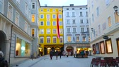 tabela : SALZBURG, AUSTRIA - MARCH 1, 2019: The dimmed evening lights of Hagenauerplatz square with historic mansions and Mozart Geburtshaus - the birthplace of famous composer, on March 1 in Salzburg
