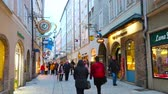 tabela : SALZBURG, AUSTRIA - MARCH 1, 2019: The pleasant evening walk through the pedestrian Getreidegasse street with fashion stores, boutiques, souvenir shops and art galleries, on March 1 in Salzburg