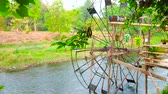 coltivazione : PAI, THAILAND - MAY 6, 2019: Watch the spinning wooden waterwheel on Pai river with lush greenery on the opposite bank, on May 6 in Pai Filmati Stock