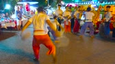 zwaarden : CHIANG MAI, THAILAND - MAY 4, 2019: Two young artists perform ritual battle dance, while musicians play drums at Saturday Night Market in Wualai walking street, on May 4 in Chiang Mai Stockvideo