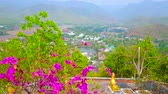 도시 : The upper terrace of Wat Phra That Doi Kong Mu temple overlooks lush bougainvillea bushes and valley of Mae Hong Son with Nong Kham lake, surrounded by Shan hills, Thailand 무비클립