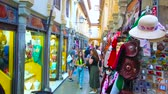 takı : GRANADA, SPAIN - SEPTEMBER 25, 2019: People shop in Calle Alcaiceria alley, that ones was Arabic Grand Bazaar, nowadays offering souvenirs, jewelry and handicrafts, on September 25 in Granada Stok Video