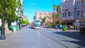 tram : SEVILLE, SPAIN - OCTOBER 1, 2019: The vibrant life in old town; the modern tram rides the Constitution avenue, where the crowds of tourists walk along historical edifices, on October 1 in Seville