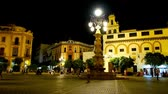 başpiskopos : SEVILLE, SPAIN - OCTOBER 1, 2019: Evening walk in Plaza Virgen de los Reyes with a view on vintage lamppost fountain with lanterns and Incarnation convent in bright lights, on October 1 in Seville Stok Video