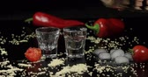 menthe poivrée : Pouring vodka into shot glasses which are placed on a black surface with pepper, sesame and cherry tomatoes.