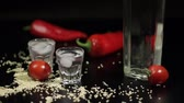 wedge : Sparse sesame seeds to two cups of vodka near bottle with vodka. On the black background there are two red peppers. Alcohol bar