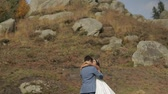 fede nuziale : Groom and bride in park near mountain hills. Bride hugs groom. Wedding couple. Happy family. Man and woman in love. Lovely groom and bride. Wedding day. Slow motion Filmati Stock