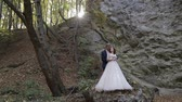veículo : Groom with bride stand in the forest park near mountain hills. Sunbeams. Wedding couple. Happy family. Man and woman in love. Lovely groom and bride. Making a kiss. Slow motion