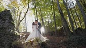 fede nuziale : Groom with bride in the forest park near mountain hills. Sunbeams. Wedding couple. Autumn season. Leaves fall off. Man and woman in love. Lovely groom and bride. Making a kiss. Slow motion