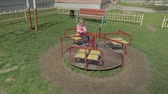 запустить : Funny cute girl is playing on schoolyard. Joyous female child having fun on playground sittinig on carousel. Slow motion
