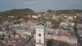 halı : Aerial Roofs and streets Old City Lviv, Ukraine. Central part of old city. European City in spring. Panorama of the ancient town. The Ukrainian flag flies on top of Town Hall, Ratush. Drone shot Stok Video