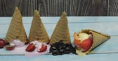 wafels : Sweet melted ice cream balls on a wooden background. Dessert with different flavors and fresh berries and fruits. Ice cream in a waffle cone. Copy space