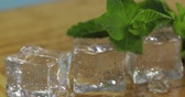 buzlu : Ice cubes and fresh mint leaves isolated on wooden cutting board. Mans hand takes mint leaves for mojito cocktail
