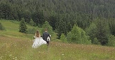 Groom with bride go for a picnic on a mountain hills. Wedding couple. Happy family. Man and woman in love. Lovely groom and bride. Wedding day