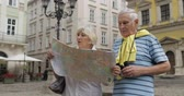 binocolo : Senior two male and female tourists walking in town with a map in hands and looking for the route while traveling in Lviv, Ukraine. Elegant woman with bag. A man with binoculars. Vacation concept Filmati Stock