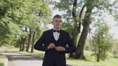 ehrgeiz : Groom, brunette young man walking in the park and fastens the jacket. Slow motion