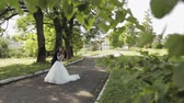 fede nuziale : Lovely young caucasian bride and groom in the park. Wedding couple. Happy family. Newlyweds. Man and woman in love. Slow motion Filmati Stock