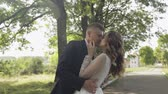 fede nuziale : Lovely young caucasian bride and groom making a kiss in the park. Wedding couple. Happy family. Newlyweds. Man and woman in love. Slow motion