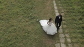Lovely young caucasian bride and groom walking in the park. Wedding couple. Happy family. Newlyweds. Man and woman in love. View from top. Slow motion