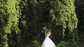 fede nuziale : Lovely young caucasian bride and groom in the park near wall with many leafs. Wedding couple. Happy family. Newlyweds. Man and woman in love. Slow motion