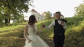 fede nuziale : Lovely young caucasian bride and groom walking in the park. Wedding couple. Happy family. Newlyweds. Man and woman in love. Slow motion