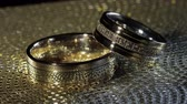 fede nuziale : Wedding gold rings lying on shiny glossy surface. Shining with light. Close-up, macro shot