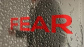 overcome fear : a business man punches against his fear and overcomes it.
