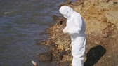 radyasyon : Female researcher in protective clothing making experiment in arid hazardous area Stok Video