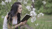 floreios : Young woman reading a book outdoor, leaning against tree, relaxing hobby Vídeos