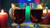 spiced : Two glasses of mulled wine stand on a blurred background of a Christmas tree, colorful Christmas lights and red candles Stock Footage