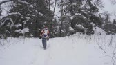pléd : Young female hiking with a backpack in beautiful winter forest, walking on a road away from the camera, light snowfall.