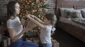 баловать : Mom and daughter give each other Christmas presents