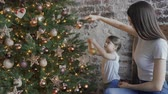 decorar : Mom and daughter decorate the Christmas tree