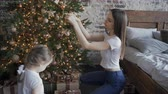 мать : Cute girl and her mother decorating Christmas tree. Young family preparing for Christmas at home